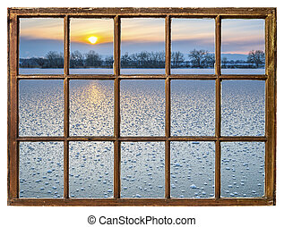 sunset over frozen lake - window view
