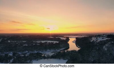 Sunset over frozen river and evergreen forest. Country...