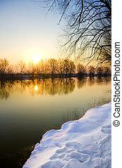 Sunset over frozen river