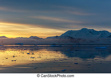 Sunset over idyllic lagoon with mountains and icebergs in the background at the Lemaire Strait, Antarctica