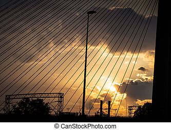 Sunset over industrial part of town - seen through suspension cables