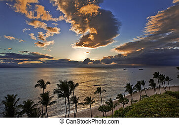 Sunset casts a golden glow over the ocean at Kaanapali Beach on Maui.