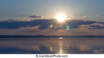 Sunset over lake. clouds. Water. Sun in the sky