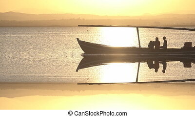Sunset over lake with tourist boat backlit with reflection -...