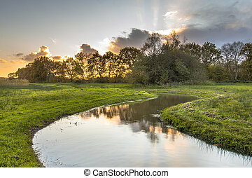 Sunset over meandering creek in small river valley in...