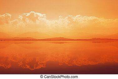 Sunset over mountain lake with reflection