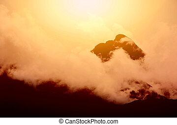Sunset over mountain peak.