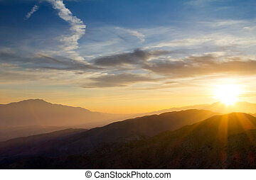 Colorful sunset rays over distant mountains in Joushua Tree National Park, California