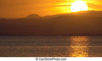 Sunset over mountains behind lake