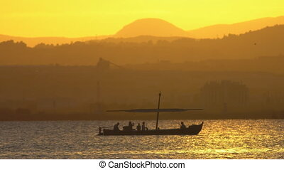 Sunset over mountains behind lake with tourist boat