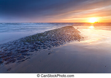 sunset over North sea coast in Netherlands
