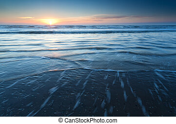 sunset over North sea waves, North Holland, Netherlands