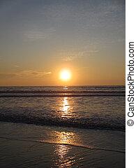 Sunset over ocean waves as they reach the beach