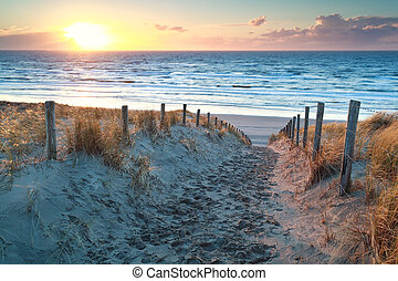 sunset over path to North sea beach