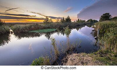 Sunset over river in dutch nature reserve Onlanden in Drenthe, Netherlands