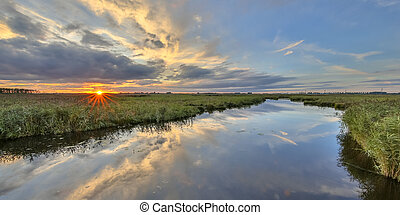 Sunset over river in marshland nature reserve