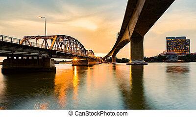 Sunset over river under bridge