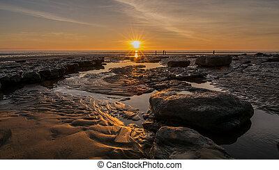 Sunset over rockpools on a beach
