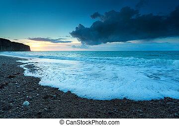 sunset over rocky beach on Atlantic ocean