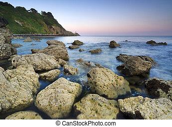 Sunset over rocky coastline