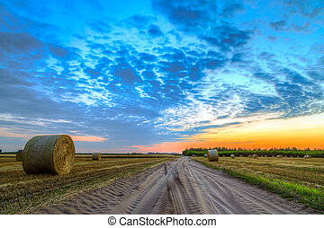 Sunset over rural road and farm field with hay bales-This photo make HDR