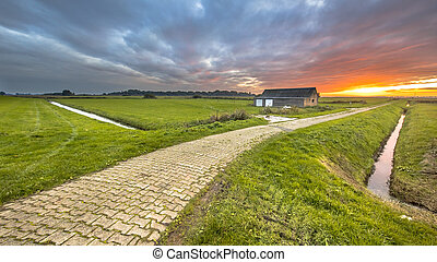 Sunset over rural road in meadow grassland