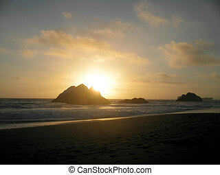Sunset over Seal rock and Pacific ocean with large cargo ship in the background on Ocean Beach