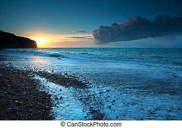 sunset over stone beach in Atlantic ocean