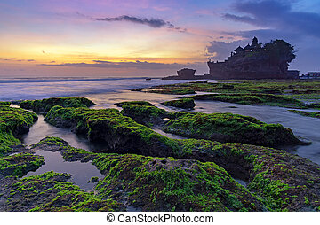 Sunset over Tanah Lot temple in Canggu, Bali, Indonesia.