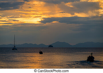 sunset over the Andaman Sea, the sun sets in the blue clouds behind the mountains
