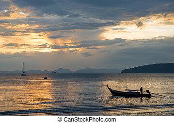 sunset over the Andaman Sea, view of the Thai traditional boats in the sea