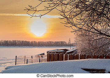 Sunset over a village vegetable garden covered with fluffy snow