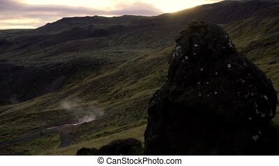 Sunset over the hilly terrain. Valley with geysers during sunset