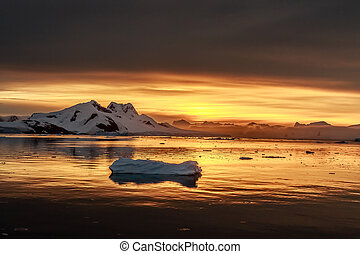 Sunset over the lagoon with drifting icebergs and snow mountains in the background, Lemaire Channel, Antarctica
