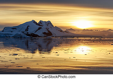 Sunset over the mountains and drifting icebergs at Lemaire Strait, Antarctica