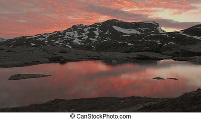 Sunset over the mountains lake. Trolltunga area, Norway. Smooth dolly shot