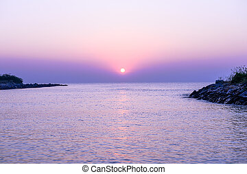 sunset over the ocean in the violet color