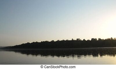 Sunset over the river, boat sails along the river