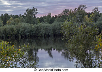 Sunset over the river overgrown with dense shrubs