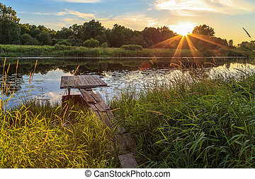 Sunset over the river, wooden bridge
