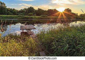 Sunset over the river, wooden bridge