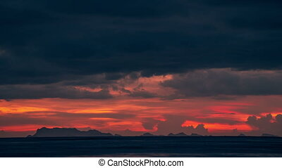Sunset over the sea and beautiful dramatic cloudscape with a view of the mountains Surat Thani, Thailand. Timelapse 4K