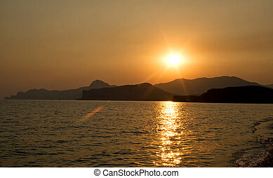 Sunset over the sea and mountains. Ukraine. Southern coast of Crimea.