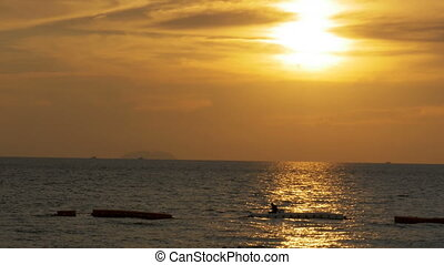 Sunset over the sea and the silhouette of a man fishing on...