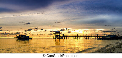 Sunset over the sea. Pier on the foreground