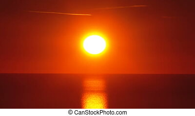 Sunset over the sea. Red big Sun sets over the horizon. Path...