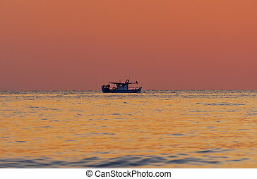 Sunset over the sea. Silhouette of fisherman boat