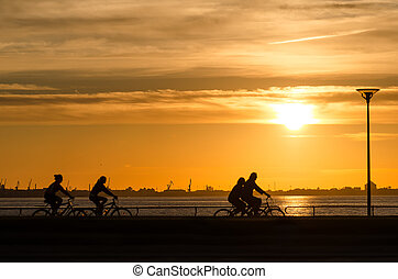 Sunset over the sea with bicyclist silhouettes