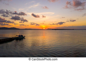 Sunset over the sea with islands. Tourist boat at the pier in the evening.