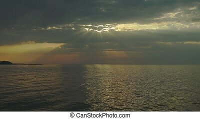 Sunset over the sea with sun rays and dramatic clouds